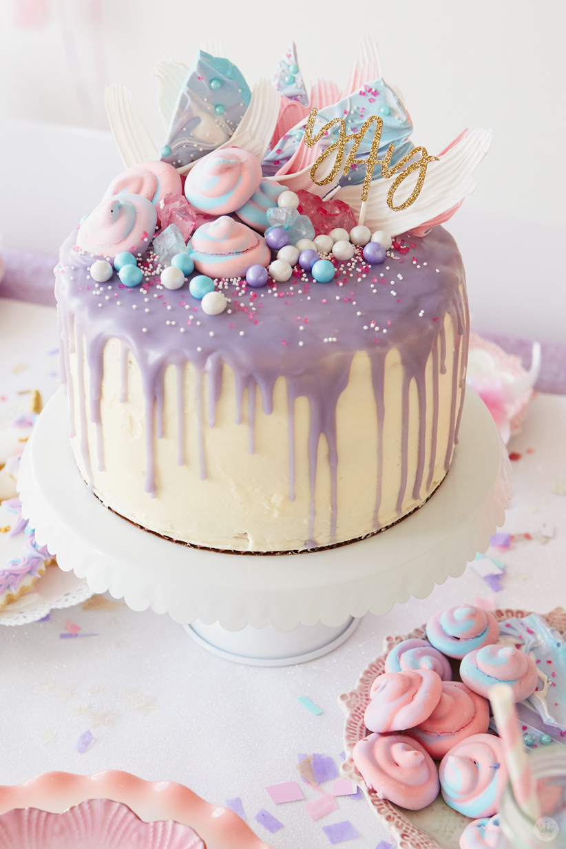 """Cake frosted in white with lavender drizzle; topped with pink and blue sprinkles, meringues, and unicorn bark and """"yay"""" lettering in gold glitter"""