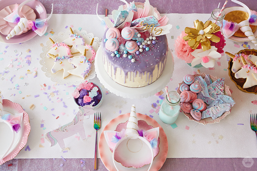 Overhead view of Unicorn Party treats: unicorn cookies, candy, meringues and unicorn bark