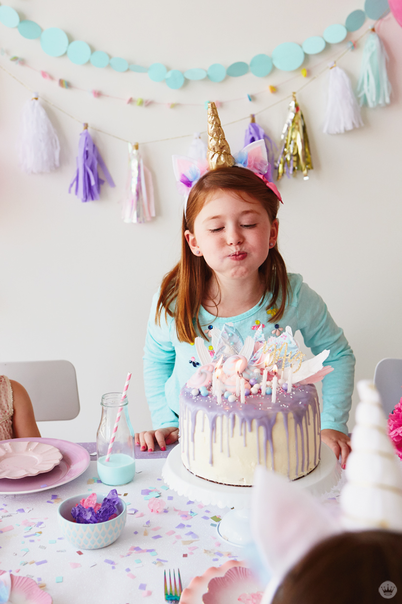 Unicorn party ideas: Girl blows out candles on unicorn cake; garlands on backdrop