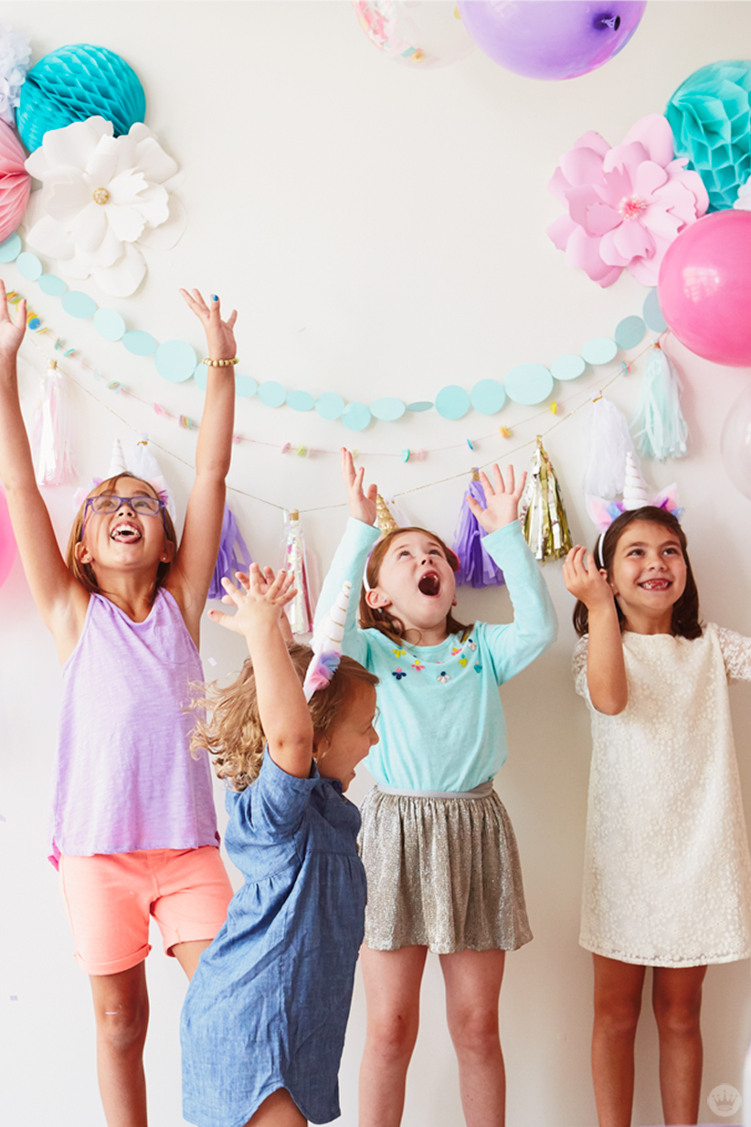 Four girls dancing and throwing balloons