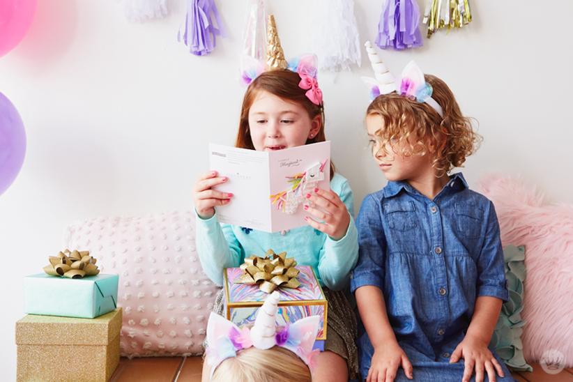 Two girls reading a Signature unicorn birthday card