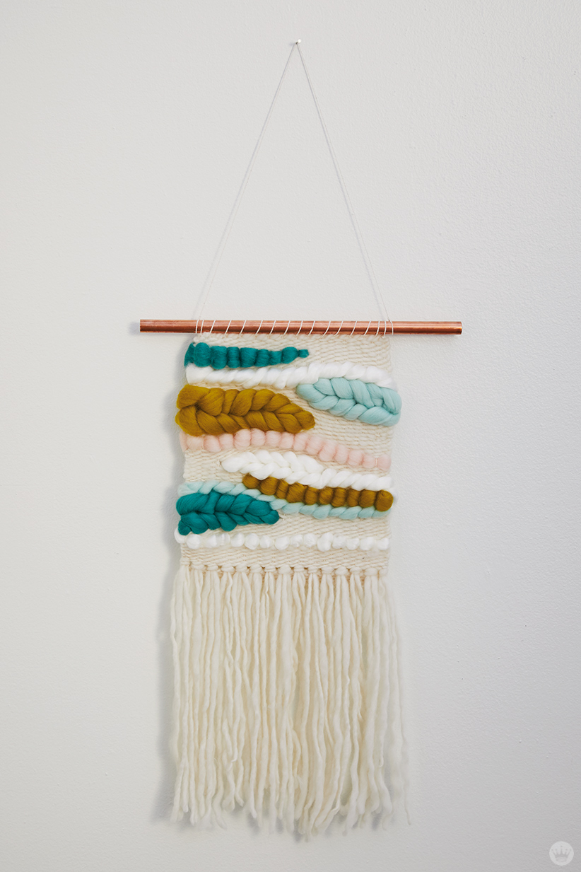 Weaving workshop: finished piece of fiber art in warm palette with tassels and roving