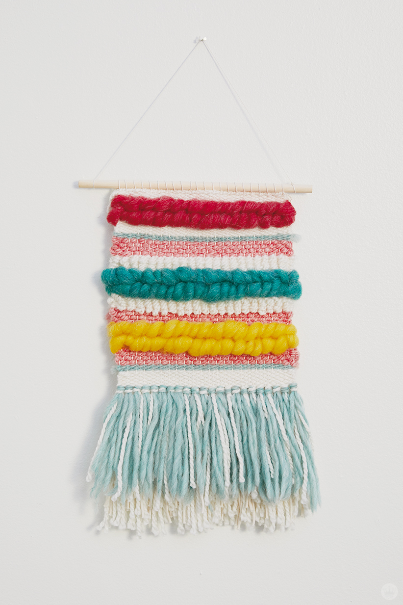 Weaving workshop: colorful finished piece of fiber art with layered tassels