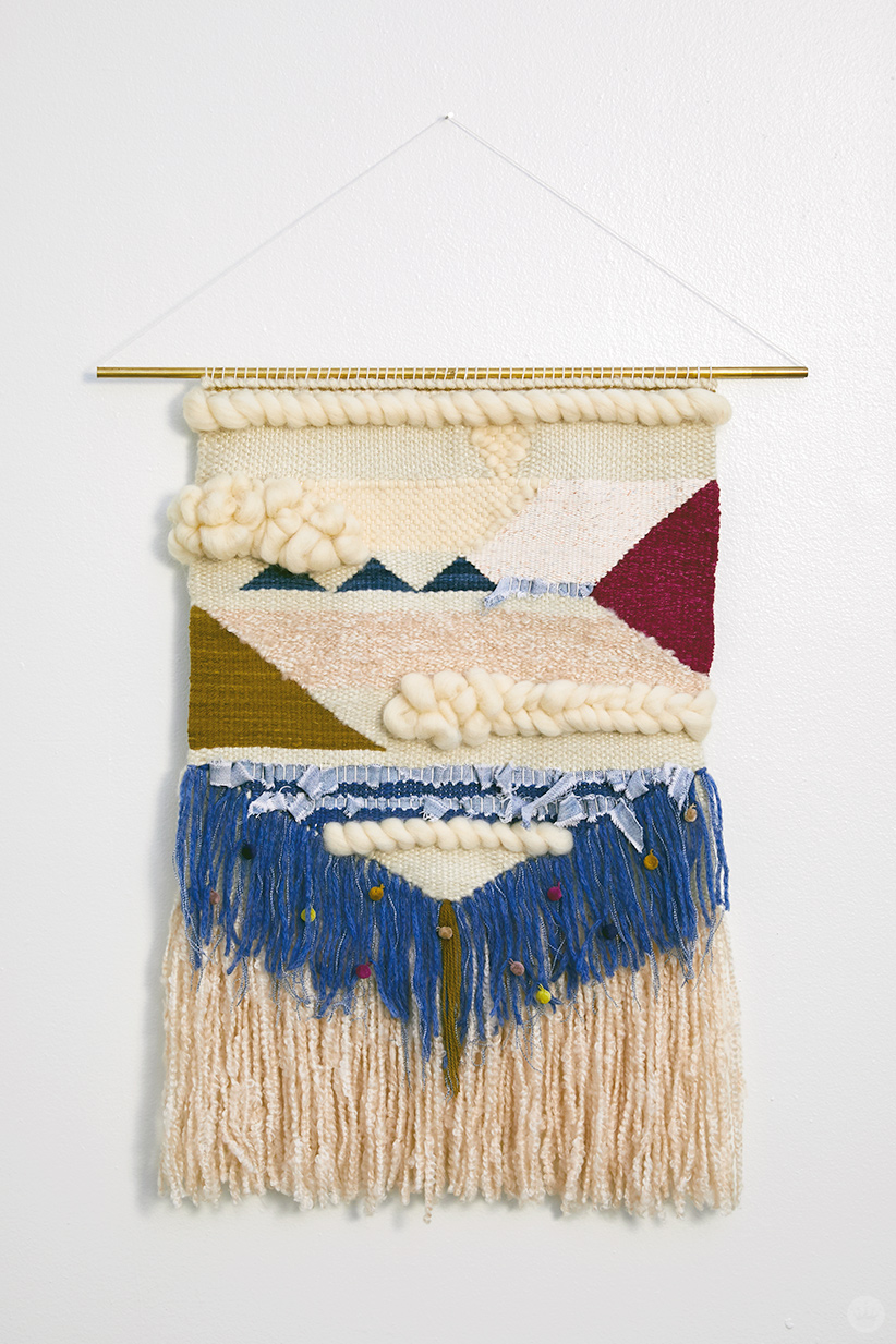Weaving workshop: finished piece of fiber art with various shapes and materials