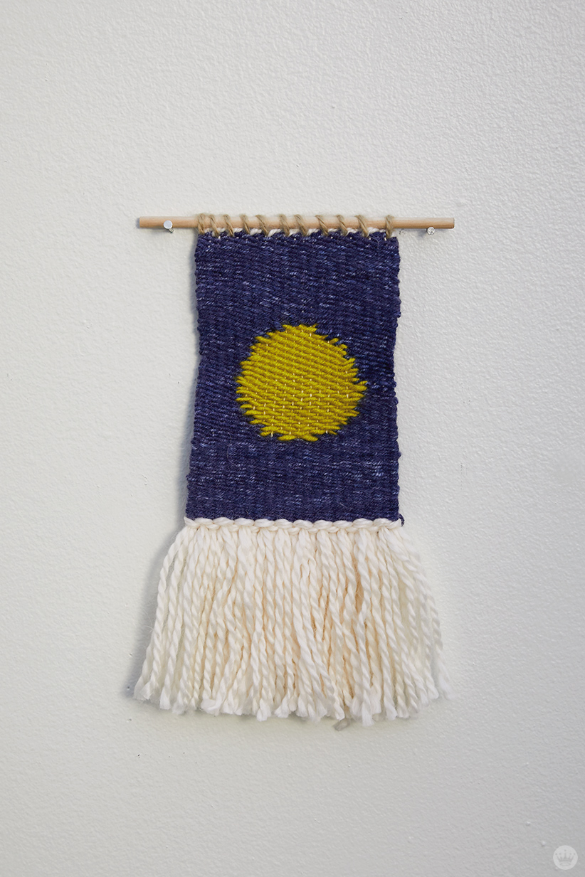 Weaving workshop: finished piece of fiber art with simple circle motif and tassels
